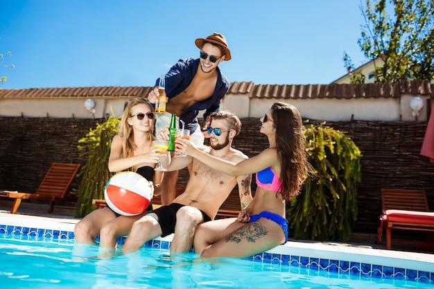 Amigos conversando, sorrindo, bebendo cocktails, descansando, relaxando perto da piscina.