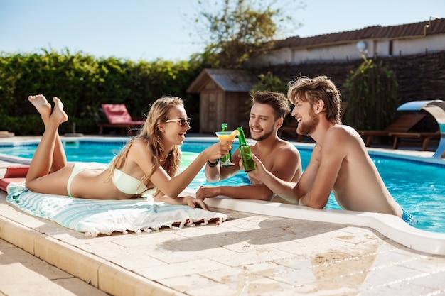 Amigos conversando, sorrindo, bebendo coquetéis, descansando, relaxando perto da piscina