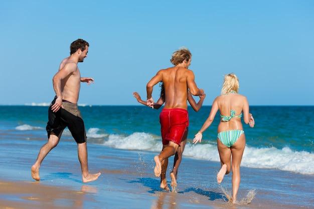 Amigos correndo de férias de praia