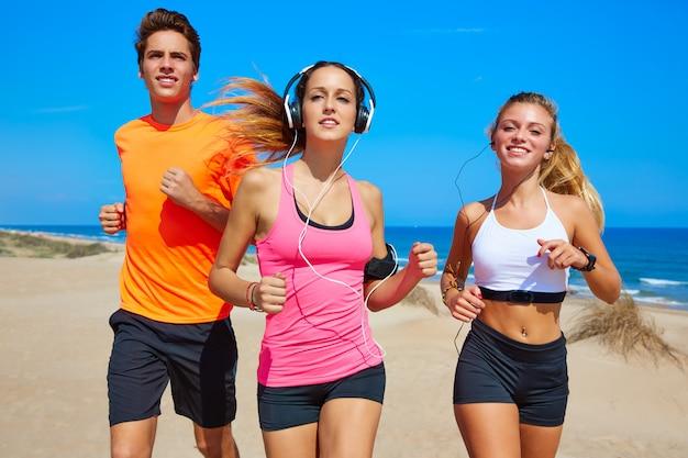 Amigos correndo na praia feliz no verão