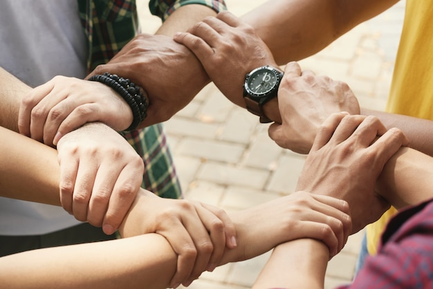 Amigos cortados segurando os pulsos de cada othe em cadeia para apoiar e colaborar