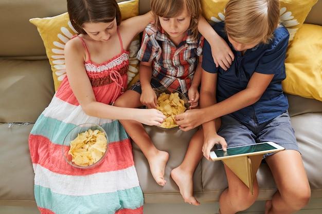 Amigos curtindo batatas fritas e desenhos animados