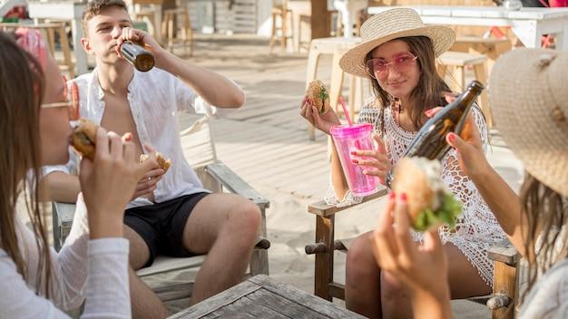 Amigos curtindo hambúrgueres ao ar livre com bebidas