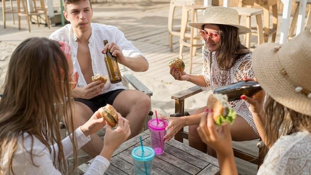 Amigos curtindo hambúrgueres ao ar livre com drinks