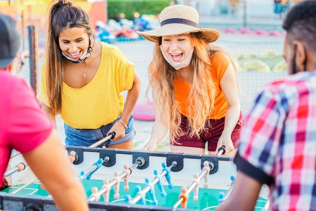 Amigos curtindo jogar futebol de mesa - jovens com máscara facial em férias