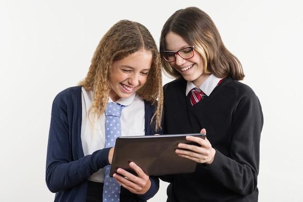 Amigos da escola são adolescentes, olhe para o tablet