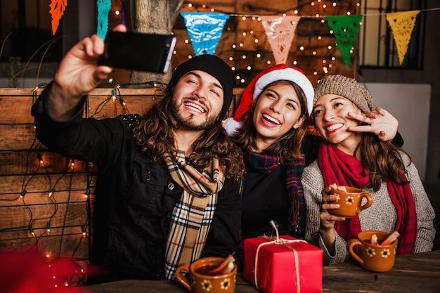 Amigos da posada mexicana comemorando o natal no méxico e tirando uma foto selfie
