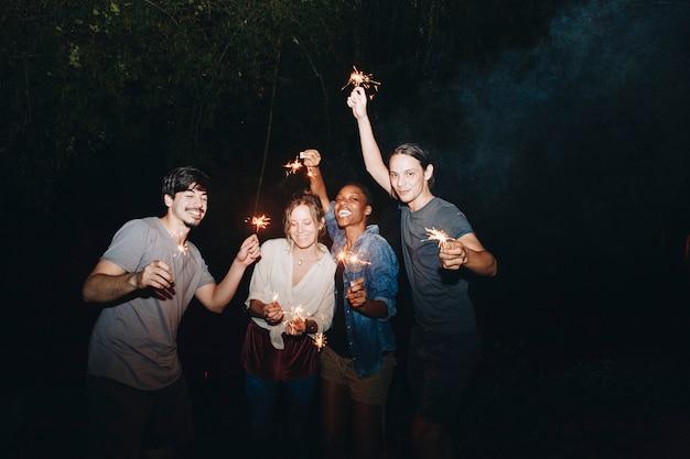 Amigos da raça misturada que jogam com a celebração dos sparklers e o conceito festivo do partido