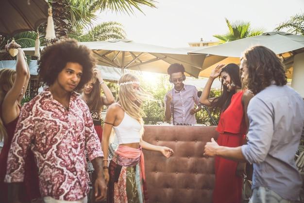 Amigos dançando em um lounge bar, com conjunto de dj