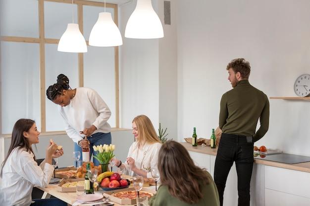 Amigos de alto ângulo almoçando em casa