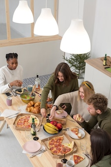 Amigos de alto ângulo em casa almoçando