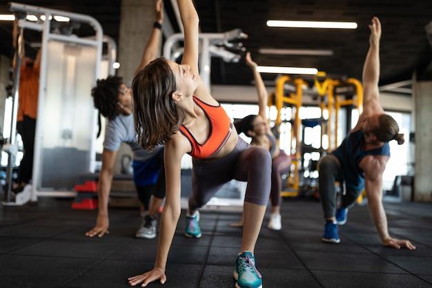Amigos de atletas jovens saudáveis fazendo exercícios no ginásio.
