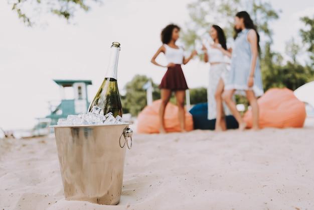 Amigos de balde de gelo de champanhe saindo na praia