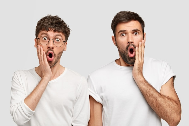 Amigos de barbudo surpresos recebem notícias chocantes, mantêm as mãos nas bochechas, olham fixamente com os olhos arregalados