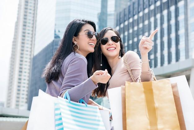 Amigos de bela jovem asiática, desfrutando de compras e viajar na cidade