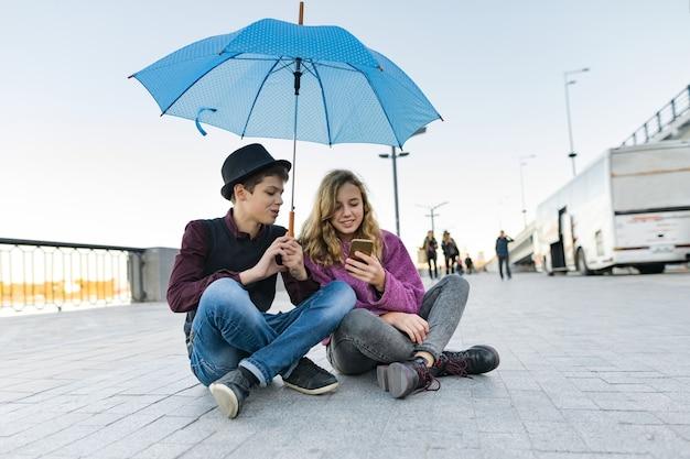 Amigos de casal sentado sob um guarda-chuva e olhando para smartphone
