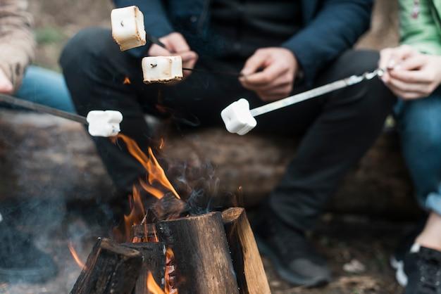 Amigos de close-up cozinhar marshmallow na fogueira