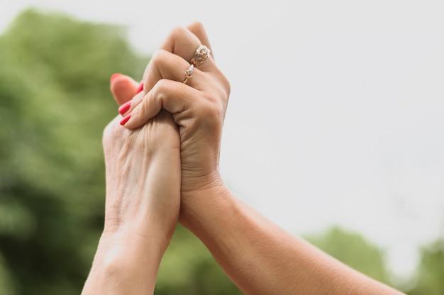 Amigos de close-up de mãos dadas