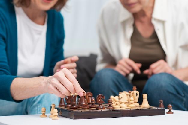 Amigos de close-up jogando xadrez juntos