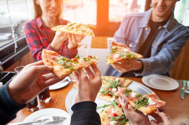 Amigos de colegas de classe comem pizza em uma pizzaria, estudantes no almoço comem fast-food