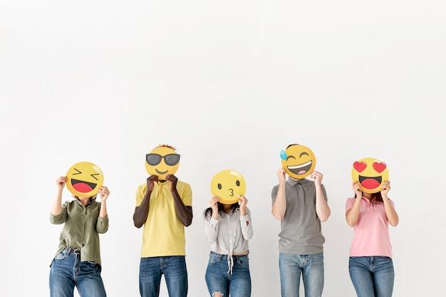 Amigos de cópia espaço cobrindo o rosto com emoji