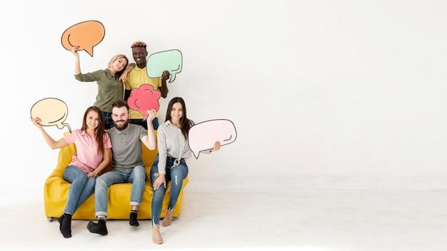 Amigos de cópia-espaço no sofá com bolha de bate-papo