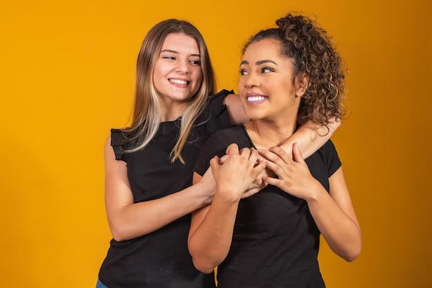 Amigos de diferentes etnias abraçados sobre fundo amarelo, o conceito de diversidade. uma mulher afro e uma loira se abraçando sorrindo olhando para a câmera