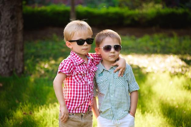 Amigos de dois filhos felizes ao ar livre em óculos de sol.