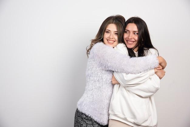 Amigos de duas meninas em pé e se abraçando.