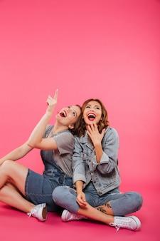 Amigos de duas mulheres felizes apontando.