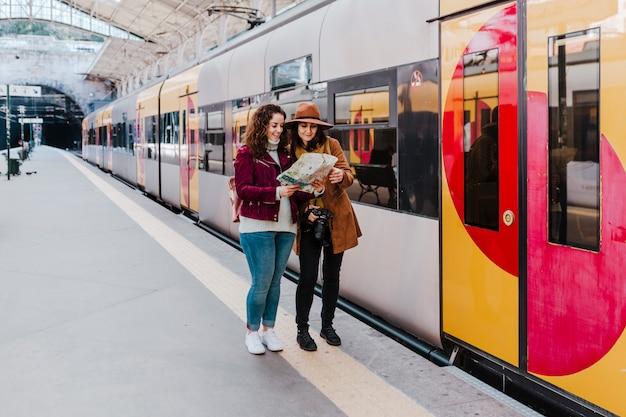 Amigos de duas mulheres na estação de trem esperando para pegar um trem e viajar. lendo um mapa e se divertindo.