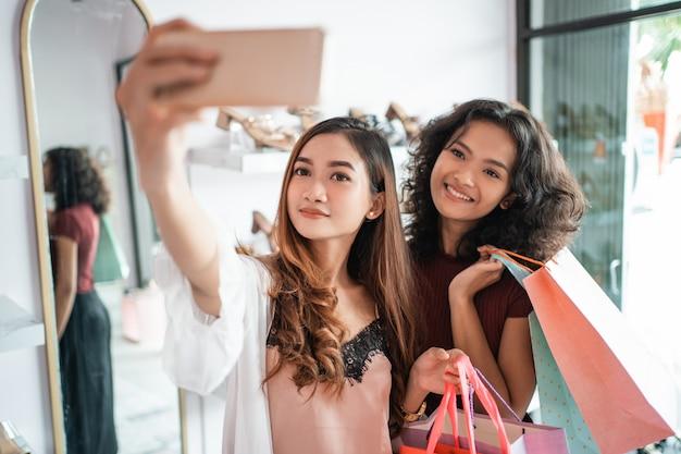 Amigos de duas mulheres tomando uma selfie enquanto fazia compras