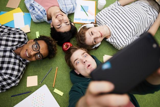 Amigos de estudante alegre tomando selfie no chão