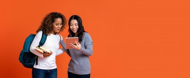 Amigos de estudantes universitários inter-raciais, olhando para o computador tablet