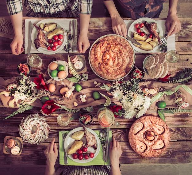 Amigos de férias ou família na mesa de férias com carne de coelho, legumes, tortas, ovos, vista superior.