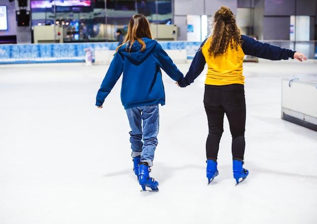 Amigos de garota de patinação no gelo na pista de gelo juntos