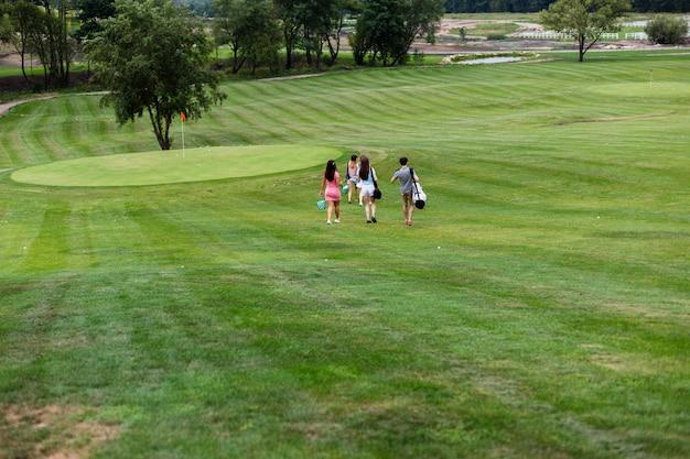 Amigos de golfe saindo do campo de golfe