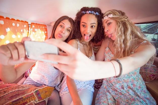 Amigos de hipster na viagem por estrada tendo selfie
