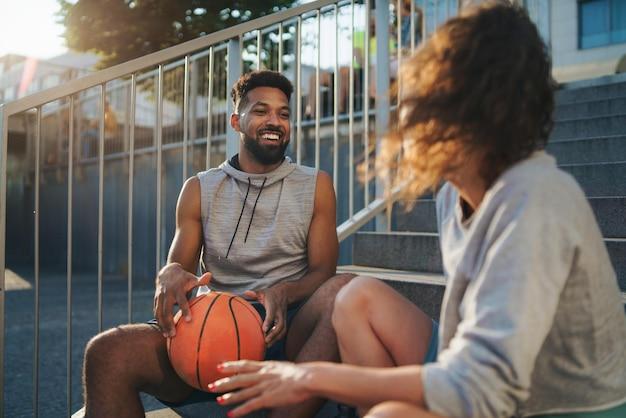 Amigos de homem e mulher com basquete descansando após o exercício ao ar livre na cidade, conversando.