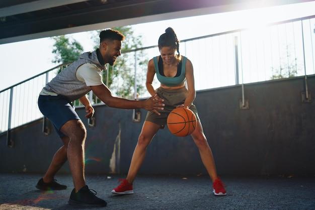 Amigos de homem e mulher jogando basquete ao ar livre na cidade.