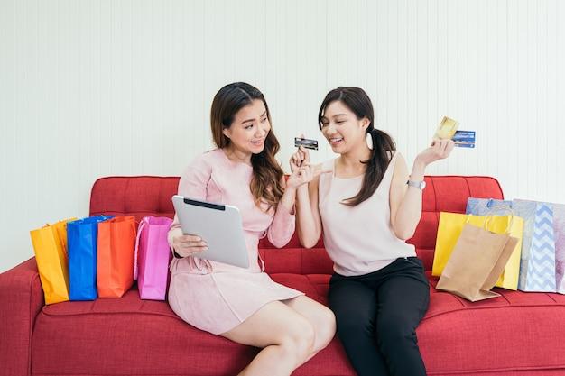 Amigos de jovem usando tablet e cartões de crédito para compras on-line juntos em casa