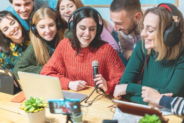 Amigos de jovens fazendo streaming on-line na plataforma de rede social - criadores de conteúdo fazendo entrevistas em feed de vídeo - genration z e conceito de tendências de tecnologia - foco no rosto da garota usando jumper vermelho