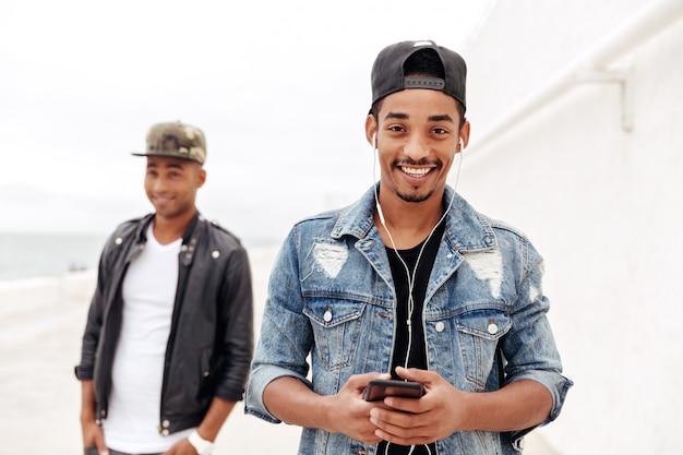 Amigos de jovens homens africanos, caminhando ao ar livre, ouvindo música.