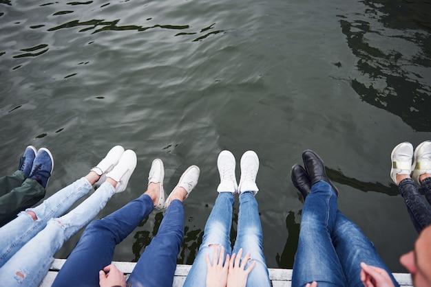 Amigos de jovens sentados na ponte sobre o rio, estilo de vida, pés sobre a água azul.