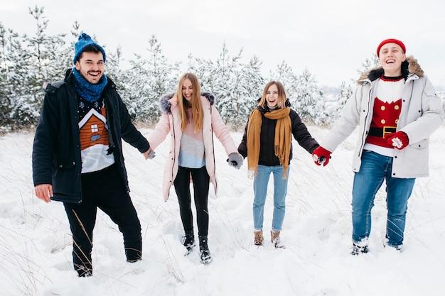 Amigos de mãos dadas na floresta de inverno