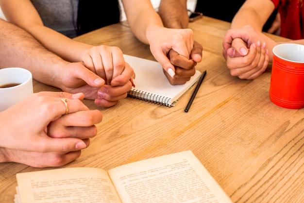 Amigos de mãos dadas perto de artigos de papelaria e copos de café sobre a mesa de madeira
