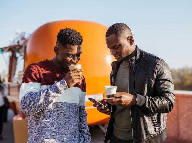 Amigos de meio de tiro tomando café em frente ao food truck