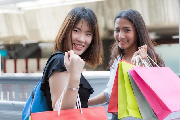 Amigos de menina asiáticas felizes com sacos de papel coloridos em shopping center
