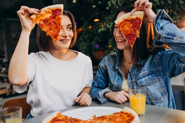 Amigos de menina com pizza em um bar na hora do almoço