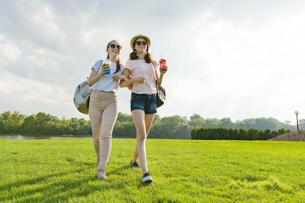 Amigos de menina estão andando no parque na natureza
